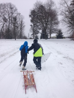 Grant and his friend Kiran sled in the snow